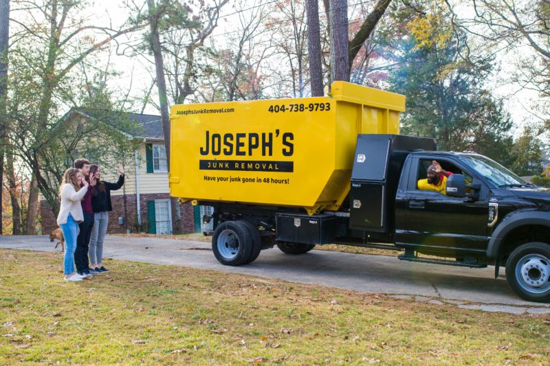 Happy clients waving goodbye to the junk removal crew