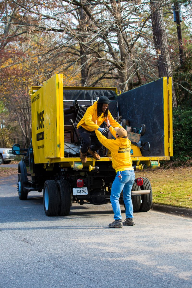 Joseph Junk Removal workers helping each other off the dump truck